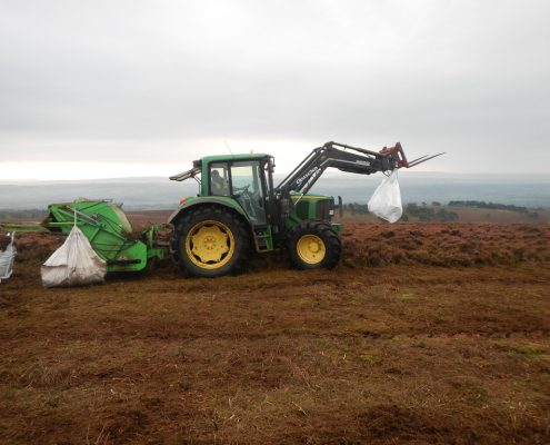 Dueled tractor fitted with a bespoke heather cutter sympathetically harvesting seed rich heather brash for bare peat moorland restoration projects undertaken by specialist environmental contractor Conservefor