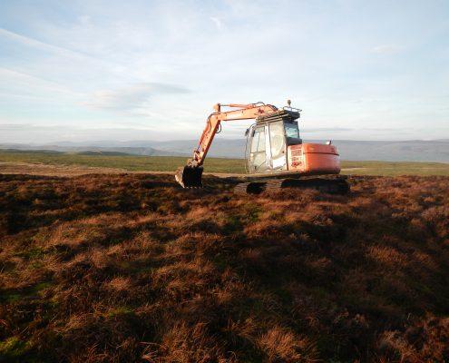 excavator installing peat dams