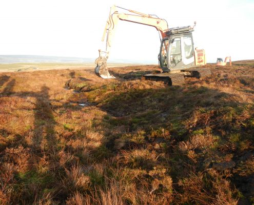 Excavator re-profiling gully on moorland
